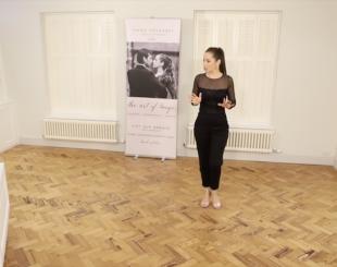 Kim explaining in a tango technique class